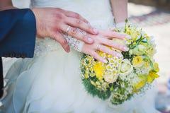 Anillos de oro y ramo de la boda imagenes de archivo