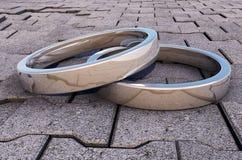 2 anillos de plata reflexivos en un pavimento Fotografía de archivo