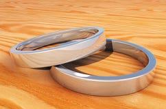 2 anillos de plata reflexivos en un tablón de madera Fotografía de archivo