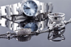 Anillos de plata y cadena de plata en el fondo del reloj de las mujeres Fotografía de archivo libre de regalías