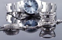 Anillos de plata y cadena de plata en el fondo del reloj de las mujeres Fotos de archivo