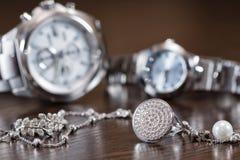 Anillos de plata y cadena que mienten en los relojes del cromo del fondo Foto de archivo libre de regalías