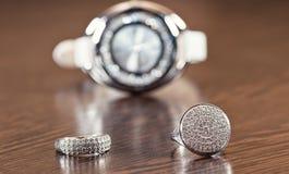 Anillos de plata y cadena que mienten en los relojes del cromo del fondo Fotografía de archivo