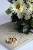 Anillos, invitación y flores de oro Fotografía de archivo