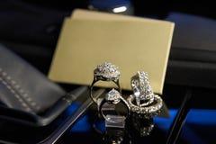 Anillos y pendientes de la joyería del diamante en el salón de un coche de lujo Foto de archivo libre de regalías