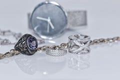 Anillos y pendientes de plata en el fondo de relojes Fotografía de archivo