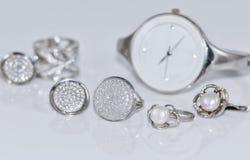Anillos y pendientes de plata en el fondo de relojes Imagenes de archivo
