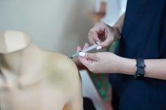 Anima di pratica dell'allievo di professione d'infermiera che intraprende la mano del mannequin nell'ambito del controllo dell'is immagine stock