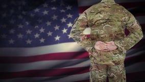 Animación de Digitaces de la situación orgullosa del soldado americano delante de la bandera americana almacen de metraje de vídeo