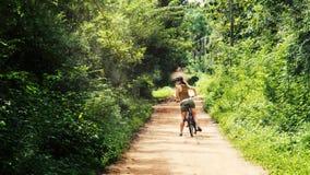 Animación de la paralaje de una muchacha que lleva un sombrero y las gafas de sol en una bicicleta, mirando sobre su hombro Admit almacen de video