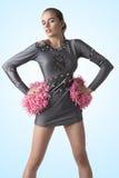 Animadora atractiva con el pompom en las caderas Imagen de archivo libre de regalías