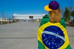 Animadora de la muchacha que dirige al estadio de fútbol con la bandera del Brasil Imagen de archivo
