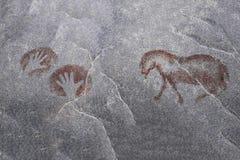 Animal antique, mains humaines sur le mur de la caverne photographie stock libre de droits