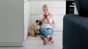 Animal doméstico de la mujer el perro mientras que usa smartphone en la cocina almacen de video