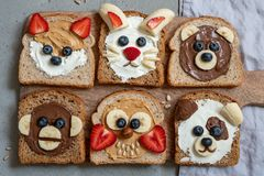 Animal faces toasts with spreads, banana, strawberry and blueberry. Funny animal faces toasts with spreads, banana, strawberry and blueberry royalty free stock photos