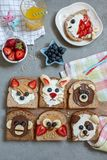 Animal faces toasts with spreads, banana, strawberry and blueberry. Funny animal faces toasts with spreads, banana, strawberry and blueberry royalty free stock photography
