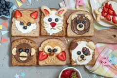 Animal faces toasts with spreads, banana, strawberry and blueberry. Funny animal faces toasts with spreads, banana, strawberry and blueberry stock photography