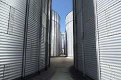 Animal feed factory. Big metal containers for grain. Modern agro-industry storage technology. Closeup royalty free stock photos