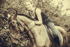 Young woman hugging and sitting on horse royalty free stock photo