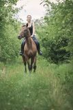 Young woman ridding on a horse. Animal, horsemanship concept. Young woman ridding on a horse through garden on sunny spring day Stock Photo