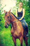 Young woman sitting on a horse. Animal, horsemanship concept. Young woman sitting and ridding on a horse through garden on sunny spring day Stock Photos