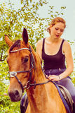 Young woman sitting on a horse. Animal, horsemanship concept. Young woman sitting and ridding on a horse through garden on sunny spring day Stock Images