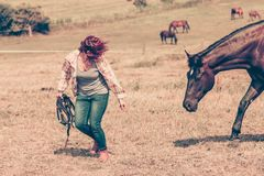 Western woman walking on green meadow with horse stock photos