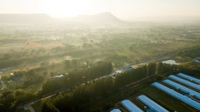 Animal livestock Farm housing in rural ranch. Surfaces on Livestock house, land and Cattle Farm in rural in Thailand with sunrise, fog and mountain background stock photo