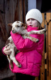 Animal love. Little girl holding a small spotted lamb Royalty Free Stock Photos