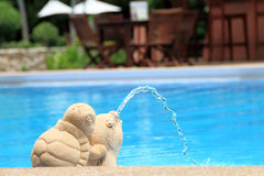 Animal sculptures spraying water in a swimming pool Royalty Free Stock Photos