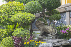 Animal stone amond the flovers in the green garden. A Chinese statue in The Grand Palace in Bangkok, Thailand Royalty Free Stock Photography