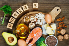 Animal and vegetable sources of omega-3. Acids as salmon, avocado, linseed, eggs, butter, walnuts, almonds, pumpkin seeds, parsley leaves and rapeseed oil stock photography