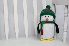 Animale farcito del giocattolo del pinguino su alto vicino bianco della sedia di oscillazione Immagini Stock