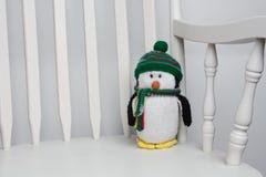 Animale farcito del giocattolo del pinguino sullo spazio bianco della copia della sedia di oscillazione Immagine Stock