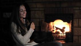 Animales domésticos y gente Mujer joven que se sienta delante de la chimenea con el animal doméstico almacen de video