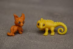 Animals children`s flame toys funny toys. Fox and yellow plastic lizard toy for children on a gray background stock images