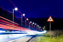 Animals crossing. Danger sign by the road at night with cars passing by Royalty Free Stock Photography