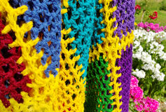 An animate from nature. Multicolored homemade blanket nex to the flowers in a garden Royalty Free Stock Image