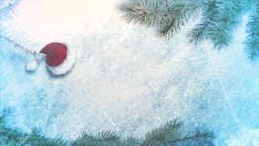 Animated closeup Christmas cap and green tree branches on shiny ice background royalty free illustration
