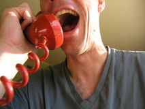 Animated converstaion. Laughing man enjoys conversation on retro phone Royalty Free Stock Image
