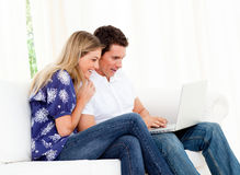 Animated couple using a laptop sitting on sofa Royalty Free Stock Photography