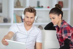 Animated couple using laptop sitting on sofa at home Royalty Free Stock Images