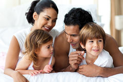 Animated family having fun lying on bed Royalty Free Stock Photos