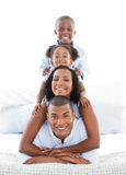 Animated family having fun lying down on bed Royalty Free Stock Photo