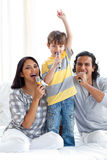 Animated family singing with microphones stock photography