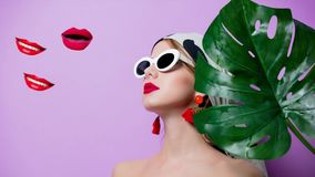 Animated portrait of beautiful style woman. In sunglasses with palm leaf on purple background stock footage