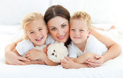 Animated siblings with their mother lying on a bed. At home Royalty Free Stock Photography