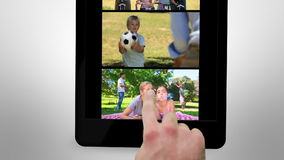 Animated tablet computer displaying videos about family leisure stock video footage