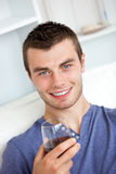 Animated young man drinking wine on the sofa Royalty Free Stock Images