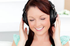 Animated young woman listening to music at home Stock Image